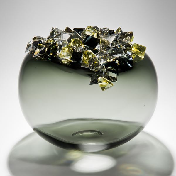 handblown spherical glass vessel in grey and green with grey black and yellow glass crystals on top