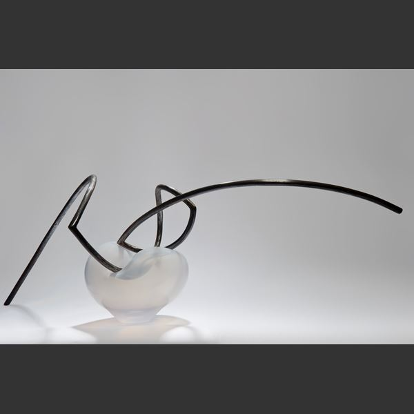 abstractly shaped pearl coloured glass dish with asymmetrical mangled thin black metal rod nestled in the centre