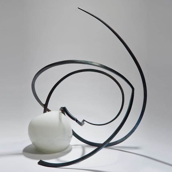 abstractly shaped pearl coloured glass sphere with asymmetrical mangled long thin black metal rod sprouting from the centre