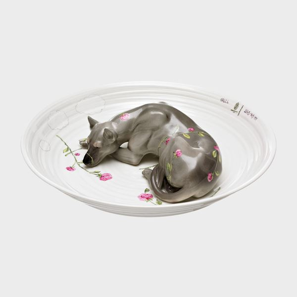 porcelain sculpted bowl in white with porcelain sculpted model of a dog resting in the centre