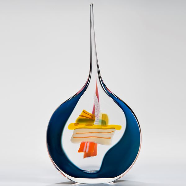 abstract glass vase with round blue and white base and long pencil thin clear top