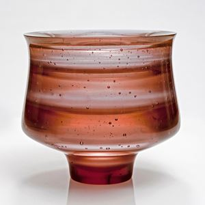short sculpted glass vessel with open top in hues of brown with pattern resembling jupiter