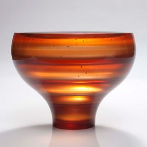 sculpted glass vessel with thin base and wide top with horizontal lined patters in orange shades