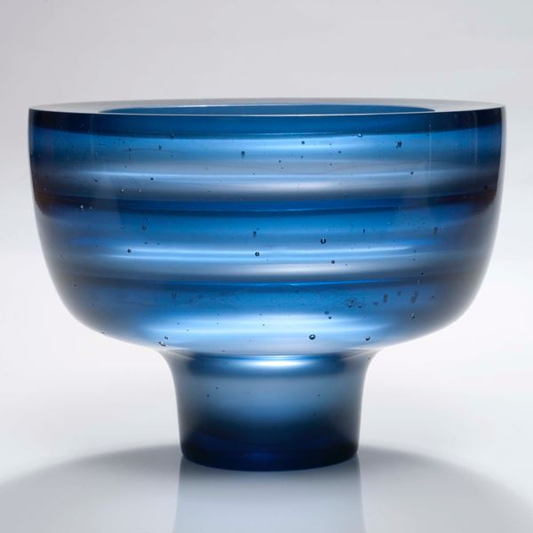 sculpted glass bowl with thin base in horizontal lined blue pattern