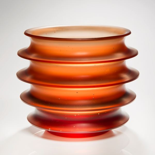 orange minimalist glass sculpture with five protruding rings