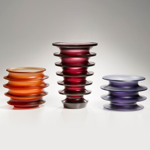purple glass sculpture with four protruding rings
