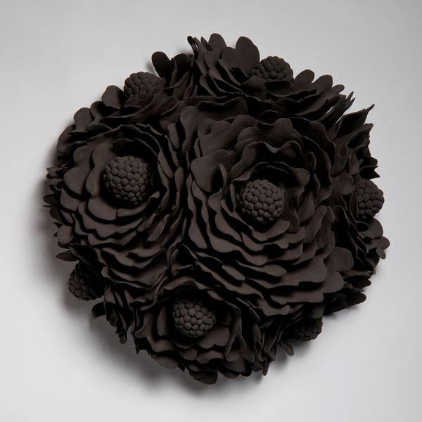 black wall hanging ceramic artwork of flowers