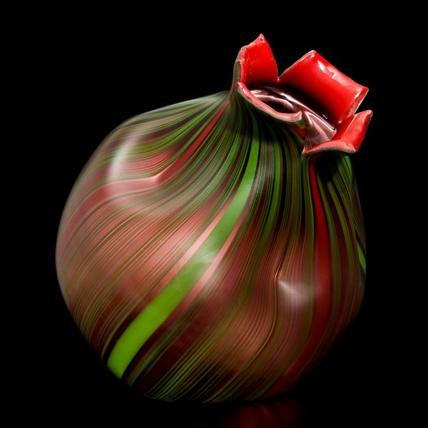 art glass sculpture resembling a nut in dark brown with green trim and red top