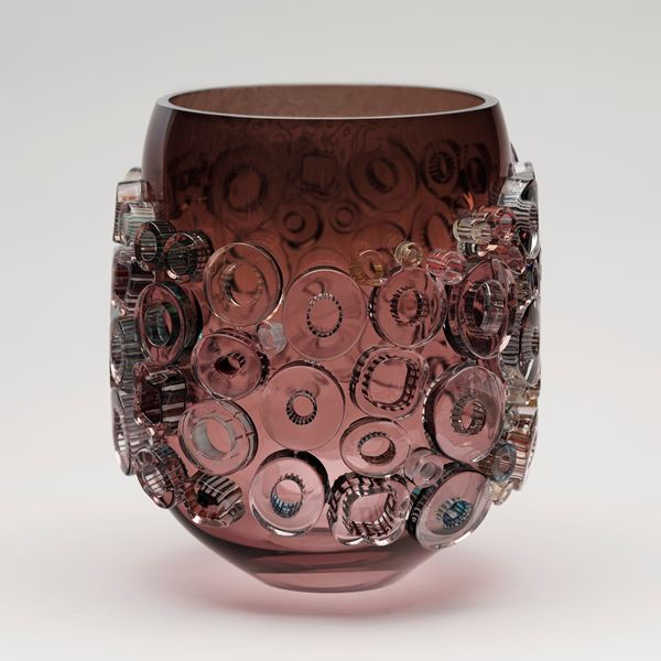pink sculpted glass vase artwork with pink yellow and green circular patterns on exterior