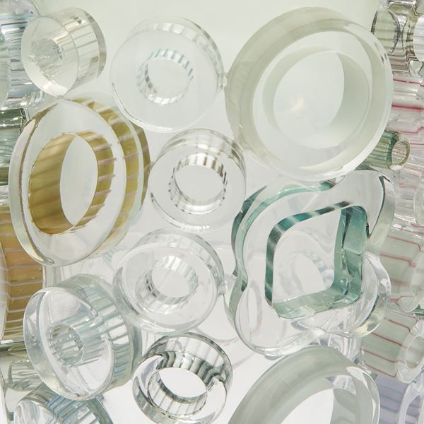 clear and green handblown glass vase sculpture with light coloured circular additions to the exterior