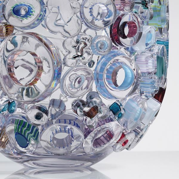 clear glass sculpted vessel with external circular glass adornments