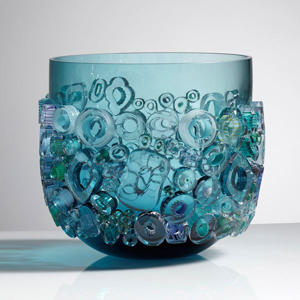 aqua blue coloured open glass vessel sculpture with busy external adornment