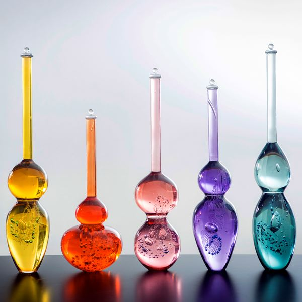 series of brightly coloured blown glass bottles with long thin necks