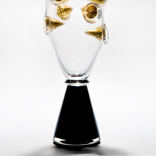 clear art glass vase with black base and embedded gold shards
