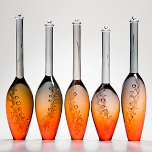 five bright orange modern glass vase sculptures with tall grey necks and engraved pattern