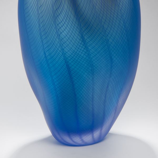 blue abstract vase like art glass sculpture with styled dent and patterned exterior