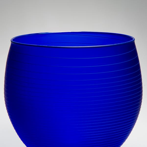 decorative glass bowl sculpture in deep blue with horizontal lines patterned throughout