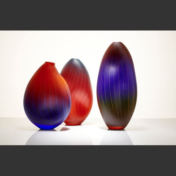 tall oblong blown glass vase in dark purple, red and black with lined and checked external engraving
