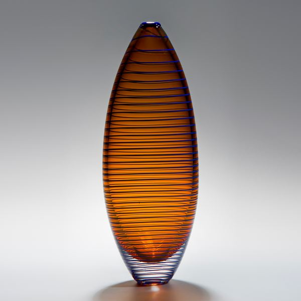 tall oval shaped amber vase sculpture with horizontal black lines