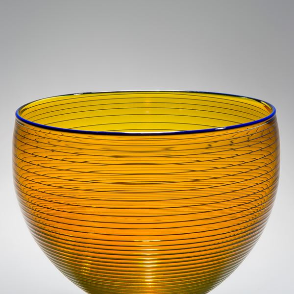 gold art glass bowl with thin black horizontal lines