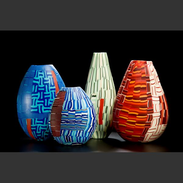 glass art vessel sculpture with blue and terracotta line patterns