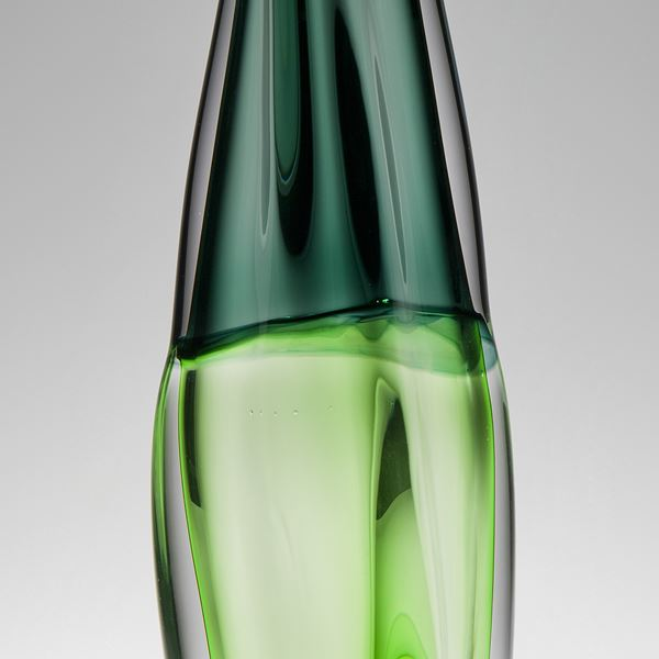 tall sculpted glass vessel in light and dark green