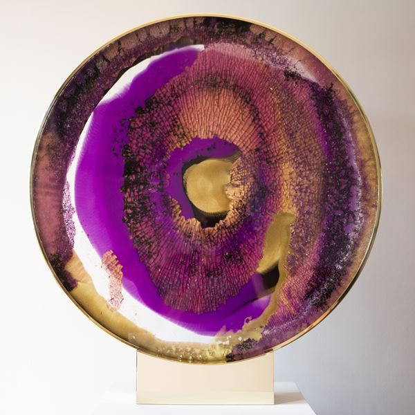 round glass art sculpture in deep purple yellow and brown resembling pattern of an eyeball