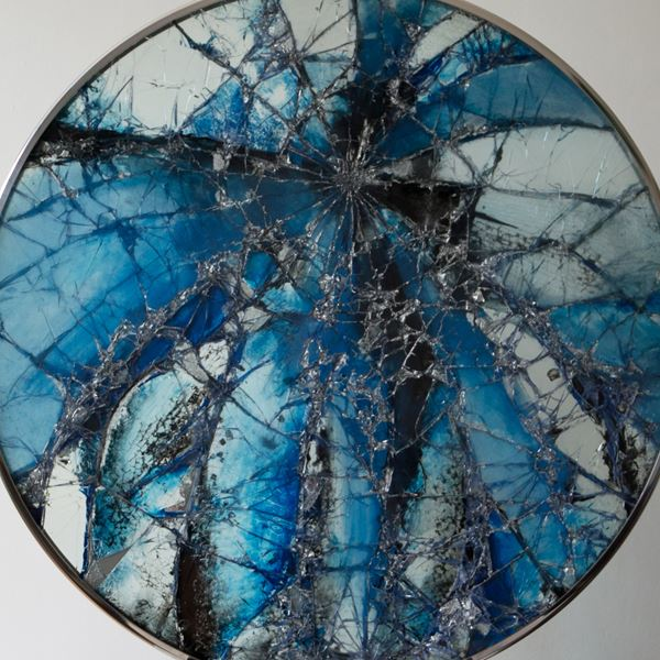 round glass art sculpture made from fragmented pieces in shades of deep blue to white and black resting on stainless steel bezel