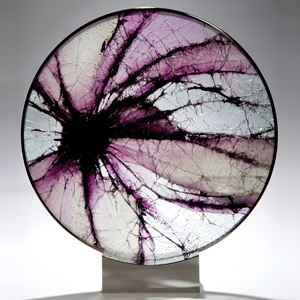 round art glass sculpture made from shattered pieces arranged in eye shape on steel base