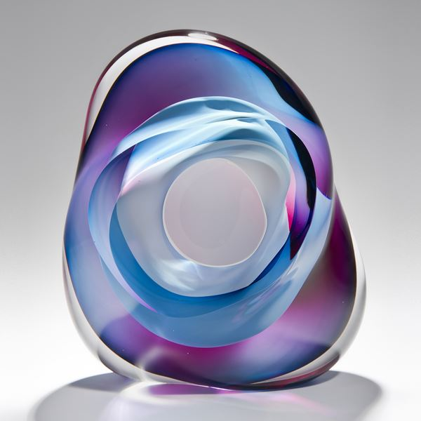 modern art glass sculpture in turquoise blue pink and purple with hole in centre