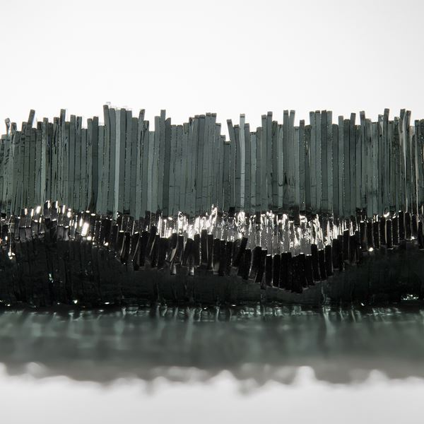 modern art-glass sculpture with hundreds of long thin dark grey shards arranged around edge to form bowl