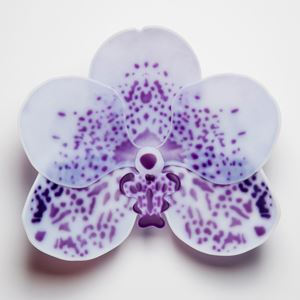 glass artwork of an exotic flower in white with purple speckles