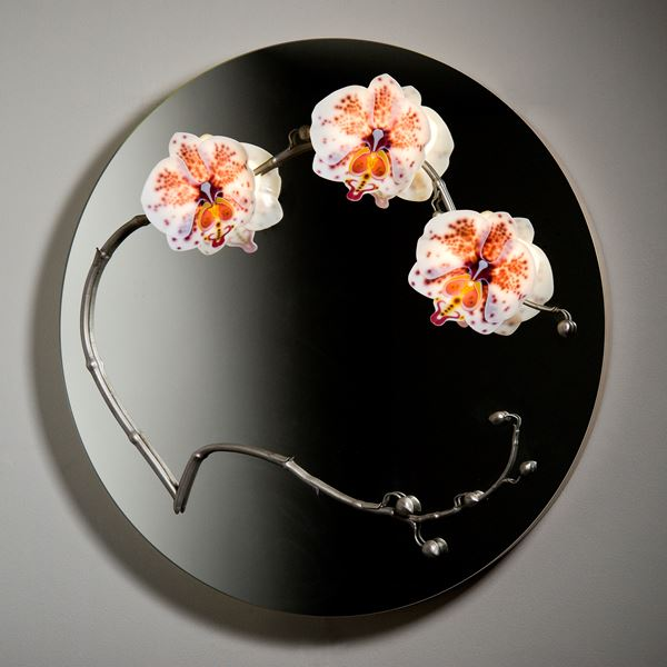 round black glass mirror with three sculpted glass orchids