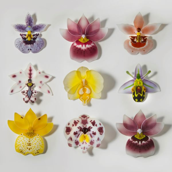 selection of bright coloured glass flower sculptures arranged on white wall-hanging background