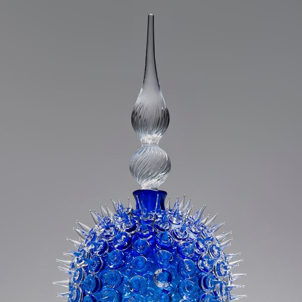 glass sculpture of spiked blue ball in the centre of clear glass base and top