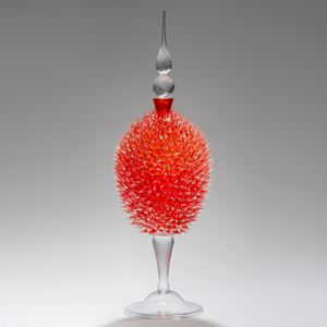 glass sculpture of spiked orange ball in the centre of clear glass base and top