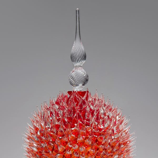 glass sculpture of spiked cherry red ball in the centre of clear glass base and top