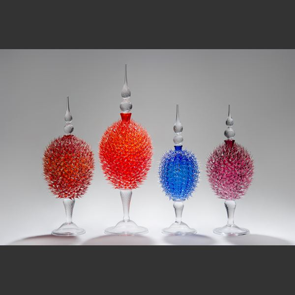 glass sculpture of spiked ruby red ball in the centre of clear glass base and top