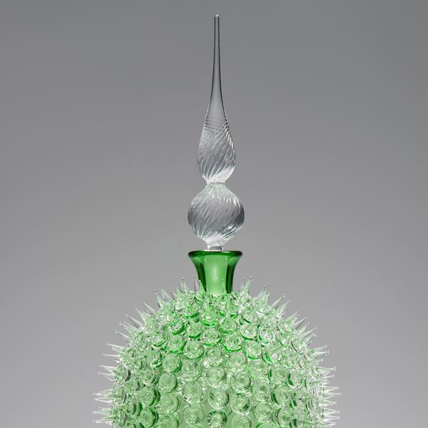 glass sculpture of spiked neon green ball in the centre of clear glass base and top