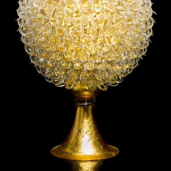 gold glass sculpture of round jar atop cone shaped base with white thistle top