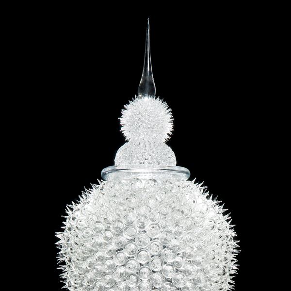 tall white glass sculpture of rounded prickly blobs on long cone with pointed top
