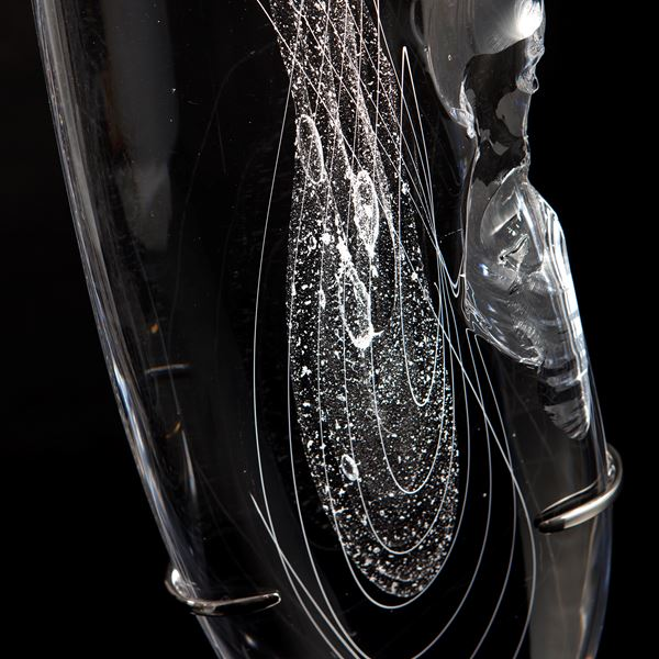 tall thin black art glass sculpture in the shape of a feather with hand chipped exterior patterns