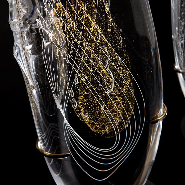 tall thin black art glass sculpture in the shape of a feather with hand chipped exterior gold patterns