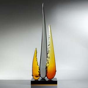 a trio of glass shards one long carbon coloured and centre flanked by two shorter amber and yellow shards resting on black metal base