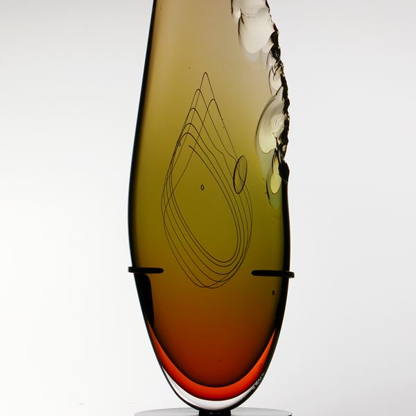 sculpted amber glass in upright feather shape resting on black base