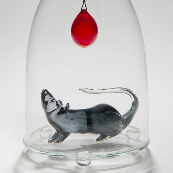 glass and steel sculpture of a mouse trapped in a clear glass flask with a crow resting on top