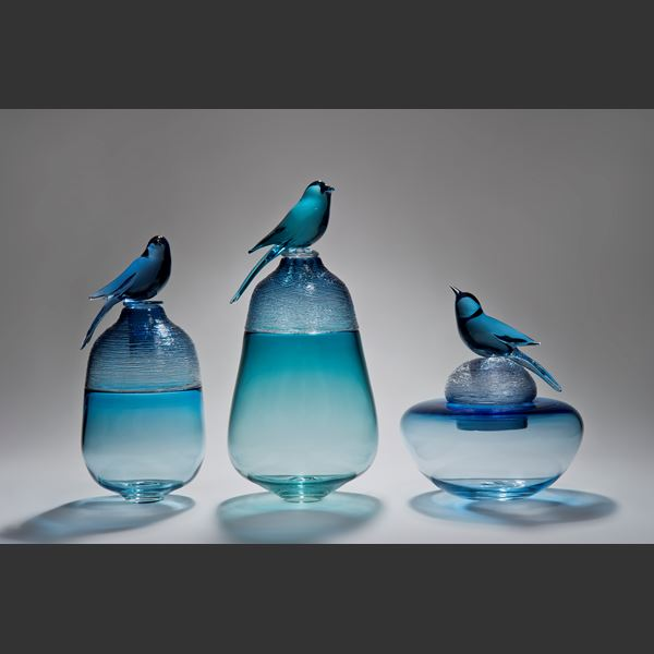 blue glass sculpture of funeral urn with bird on top