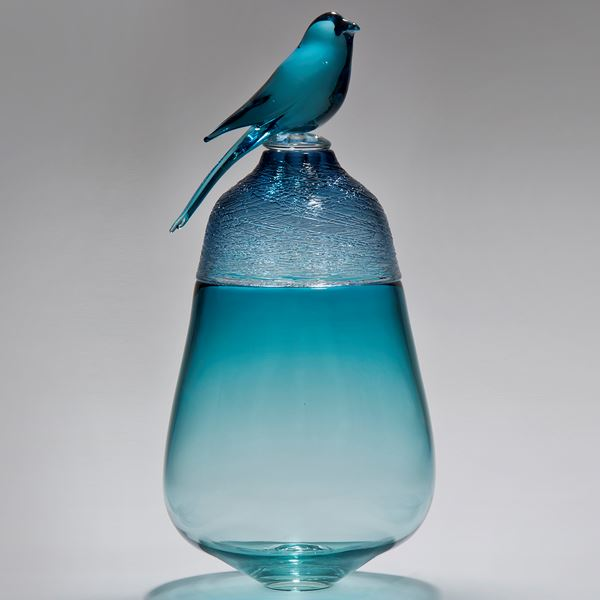 light blue coloured glass artwork of bird sat on top of vessel