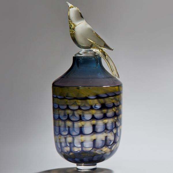 glass artwork of bird sat on top of funeral urn in blue purple yellow and gold