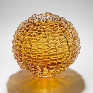 sphere shaped blown glass sculpture in amber made from stacked small shards